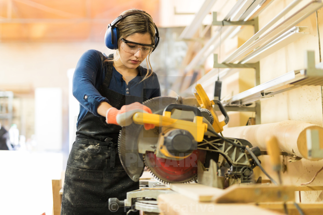"""Woman using power tools in a woodshop"" stock image"