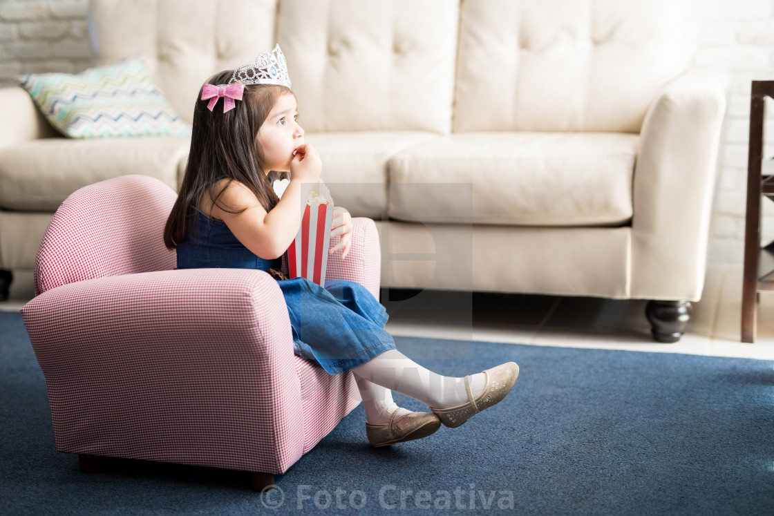 """Baby with princess crown watching tv at home"" stock image"