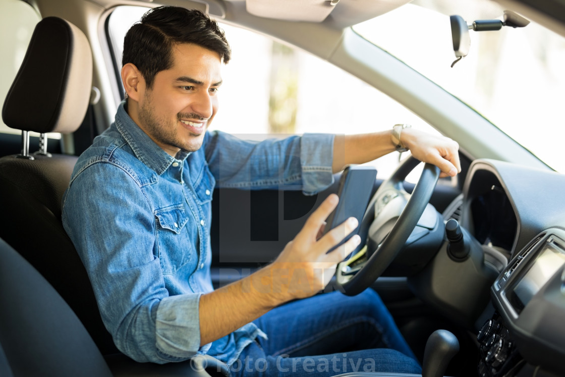 """Man using phone while driving car"" stock image"