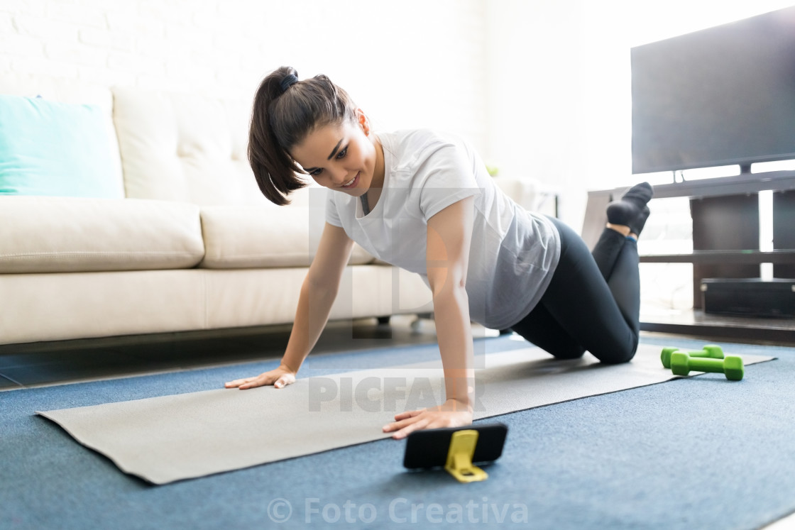"""Woman exercising watching online videos"" stock image"
