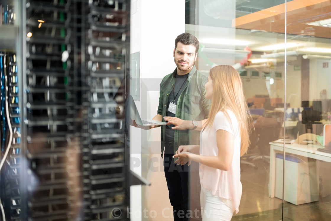 """Colleagues discussing in office server room"" stock image"