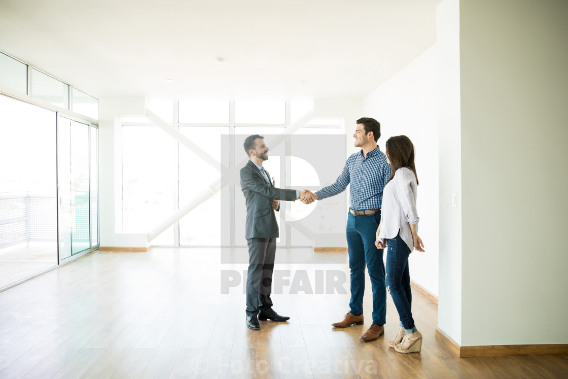 """Estate Agent Greeting Couple During Visit To New Home"" stock image"