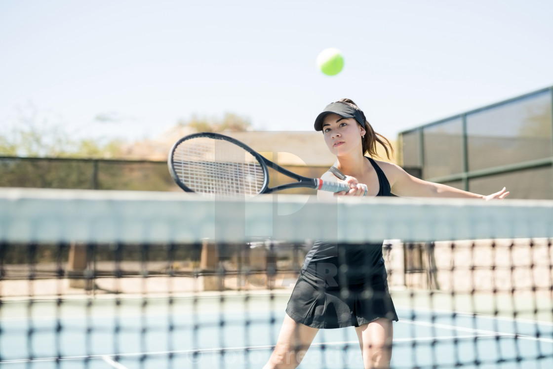 """Female tennis player practising on court"" stock image"