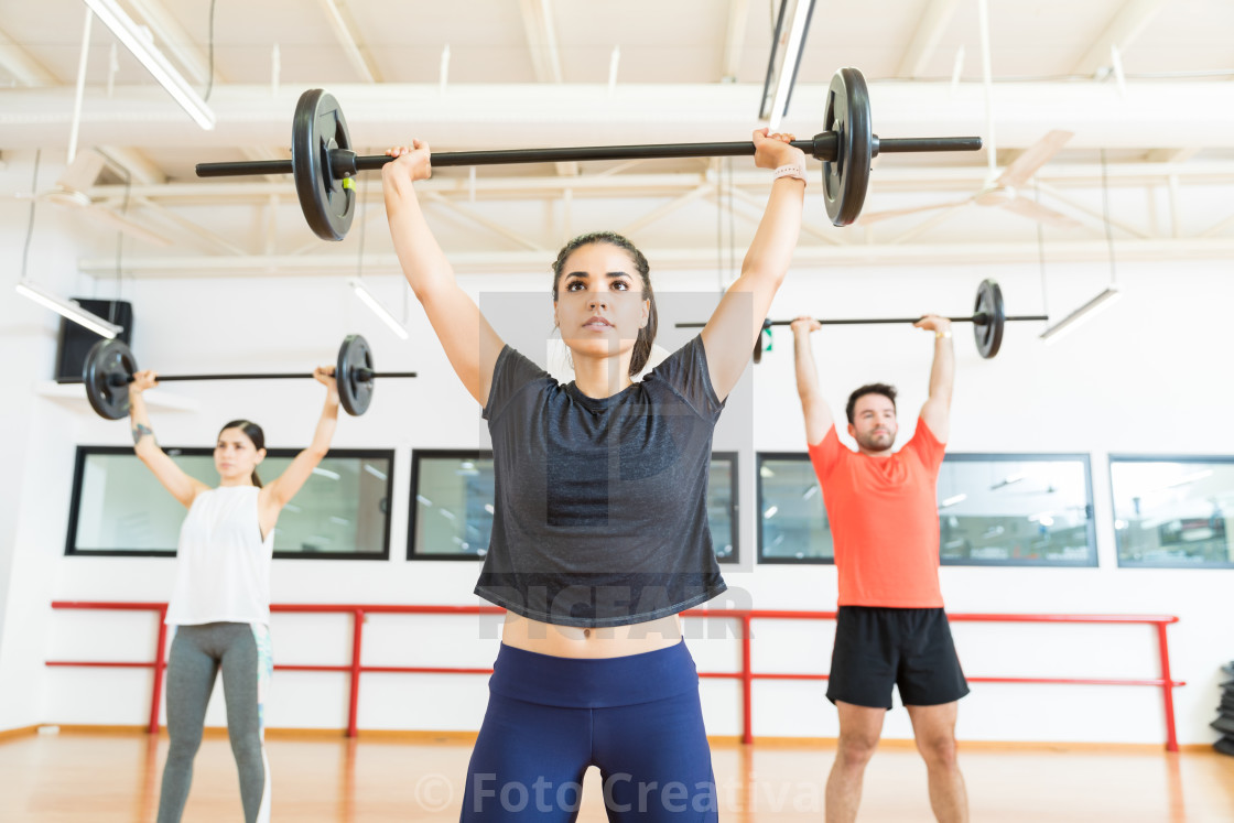 """Strong Female Lifting Barbell In Health Club"" stock image"