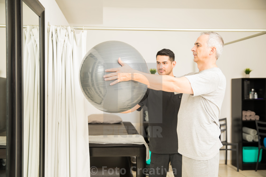 """Physiotherapist Assisting Elderly Man Lifting Exercise Ball"" stock image"