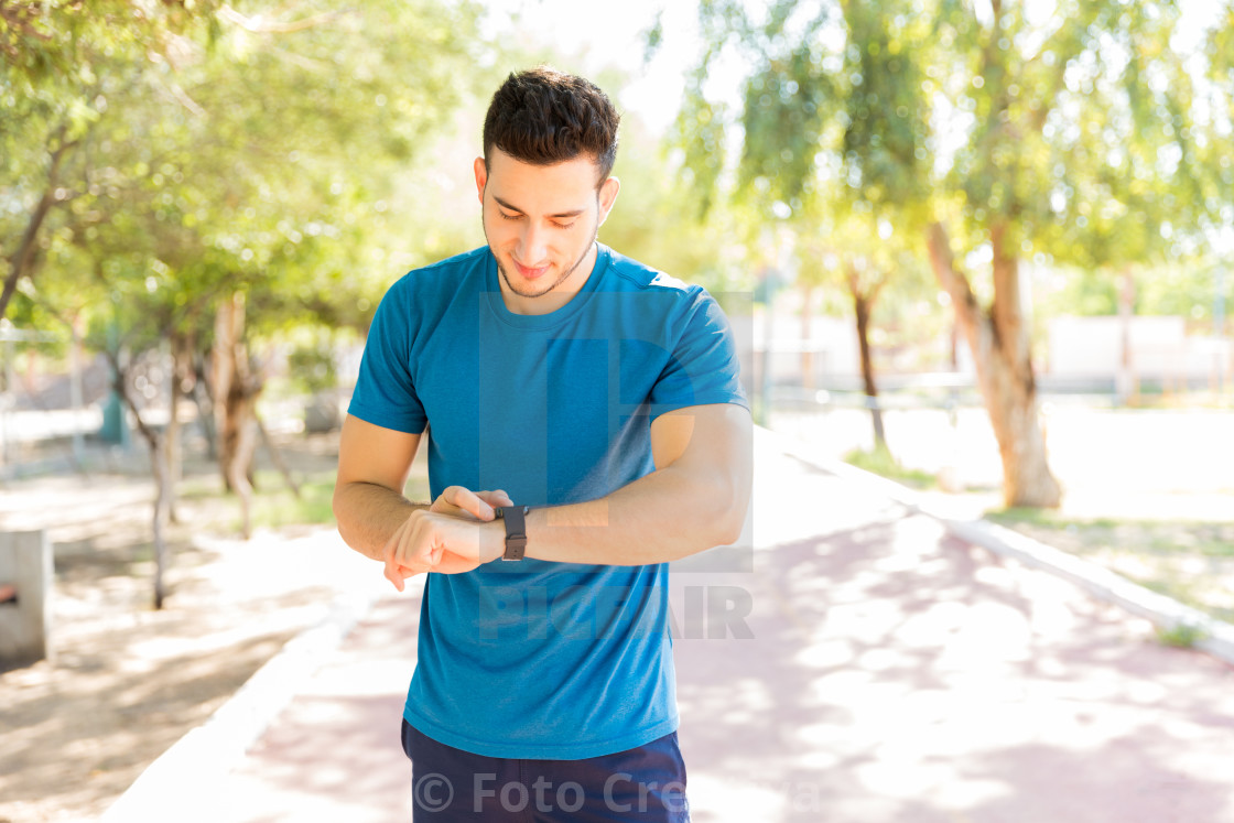 """Man Checking Counts Of Steps On Smart Watch In Park"" stock image"