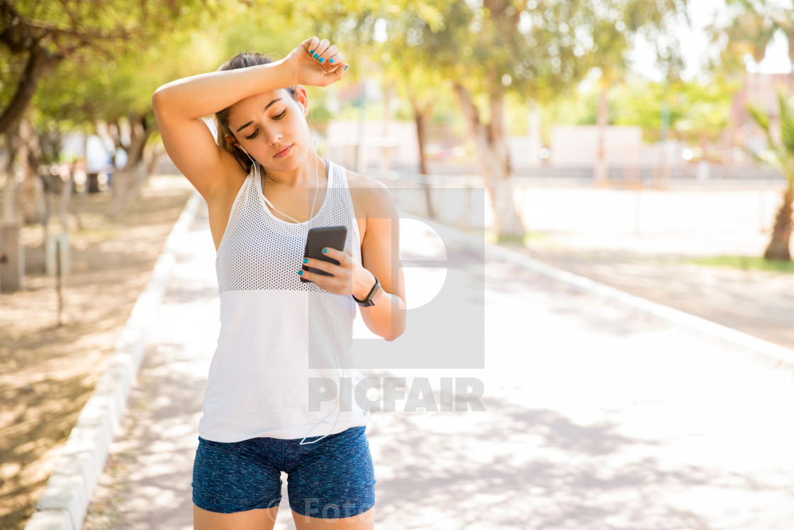 """Tired woman listening music during workout break"" stock image"