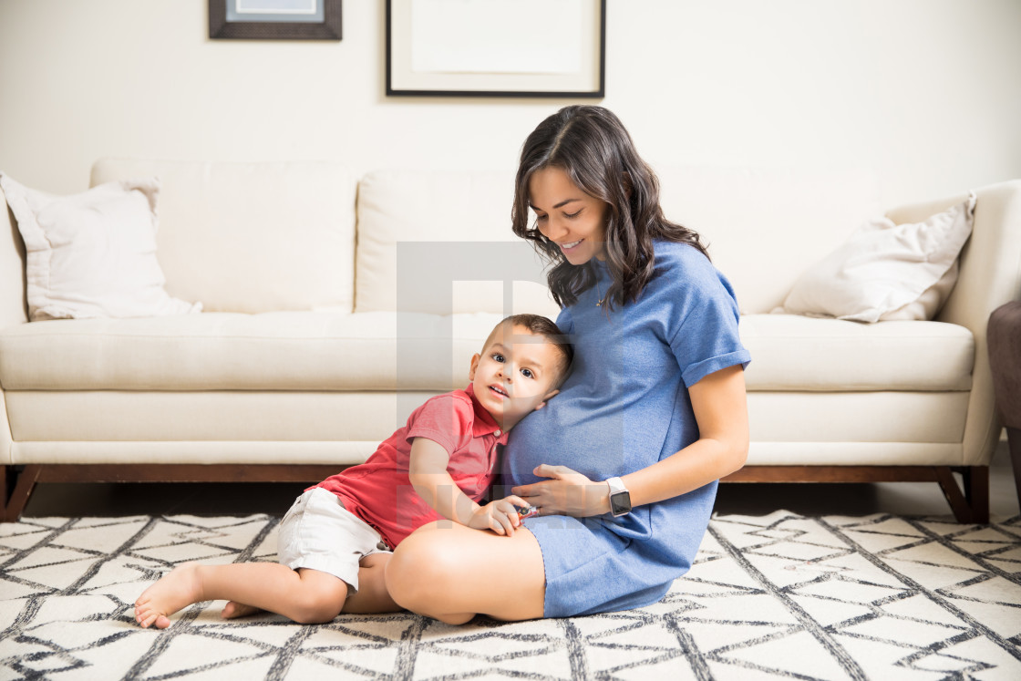 """Curious Boy Listening To Mother's Pregnant Tummy"" stock image"