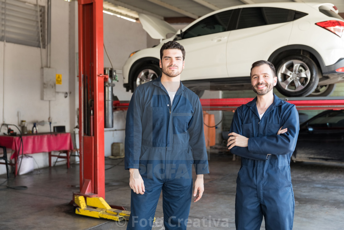 """Colleagues Wearing Uniforms While Standing Together In Garage"" stock image"