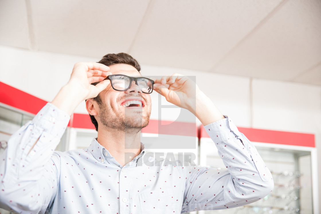 """Happy young man buying new spectacles from optical store"" stock image"