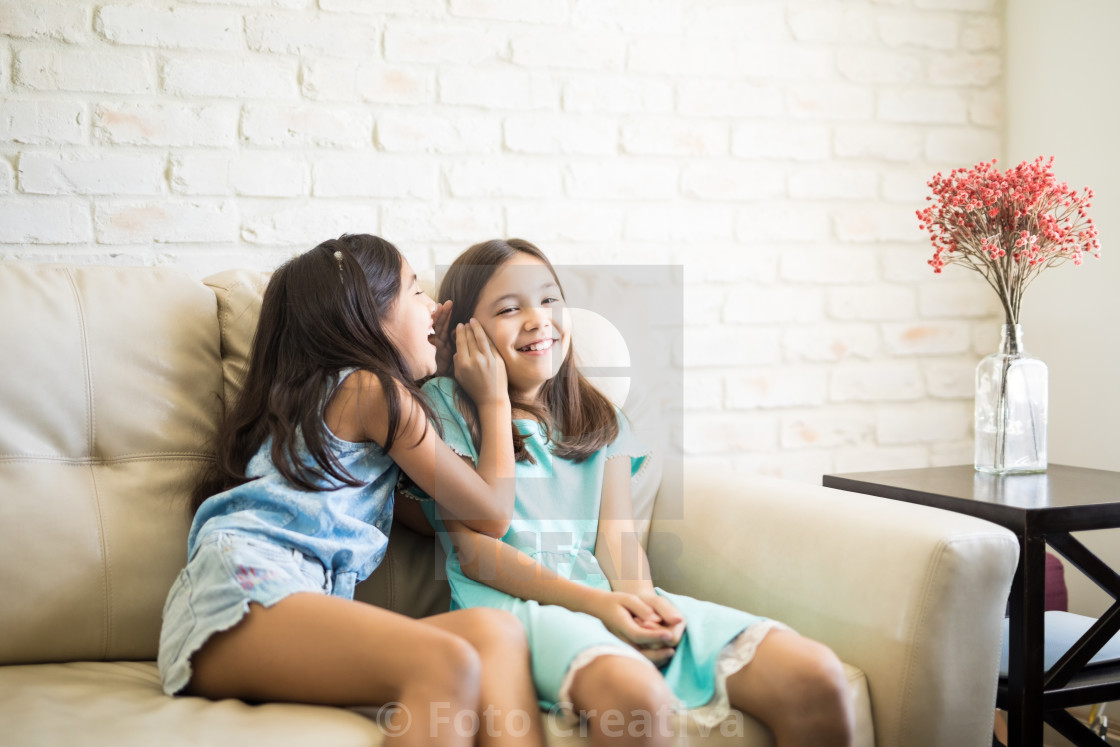 """Happy little girls whispering and sharing a secret"" stock image"