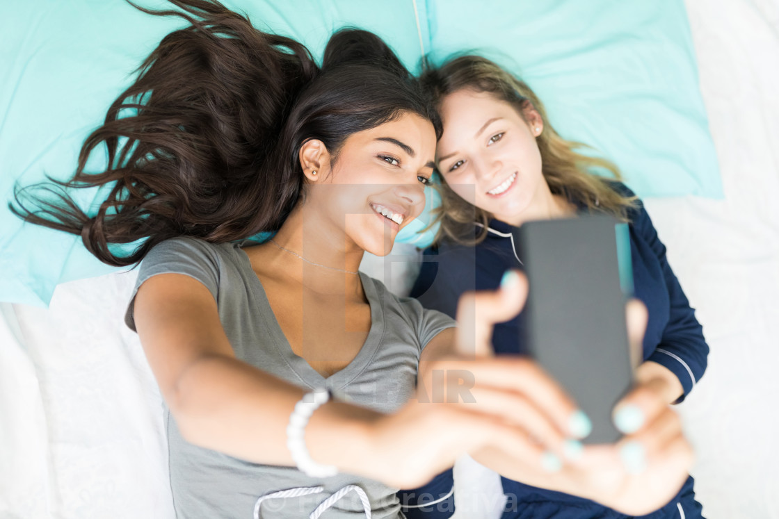 """Women Photographing Themselves On Smartphone While Resting In Bed"" stock image"