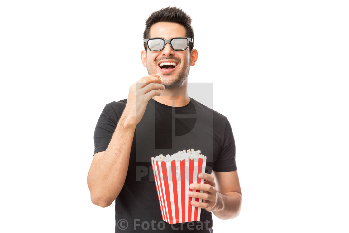 """Smiling Young Man Watching 3D Movie While Eating Popcorn"" stock image"
