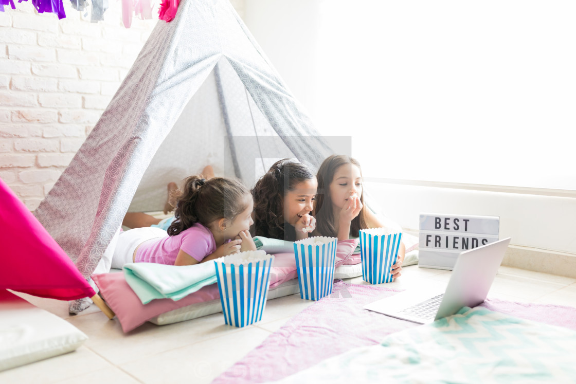 """Female Friends Enjoying Snacks While Watching Laptop In Tent"" stock image"