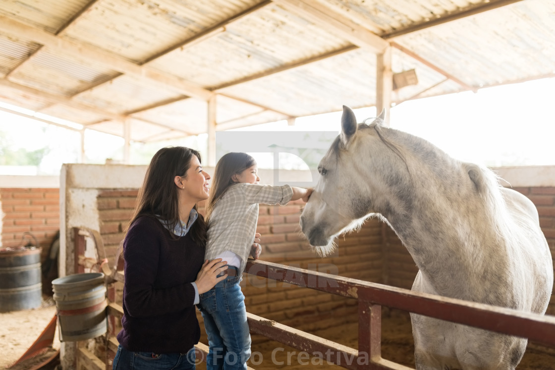 """Woman With Daughter Touching Horse In Barn"" stock image"