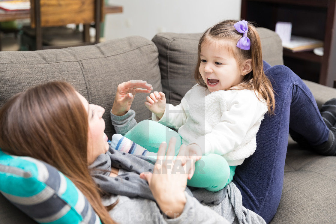 """Girl Screaming While Playing Peekaboo With Mother"" stock image"
