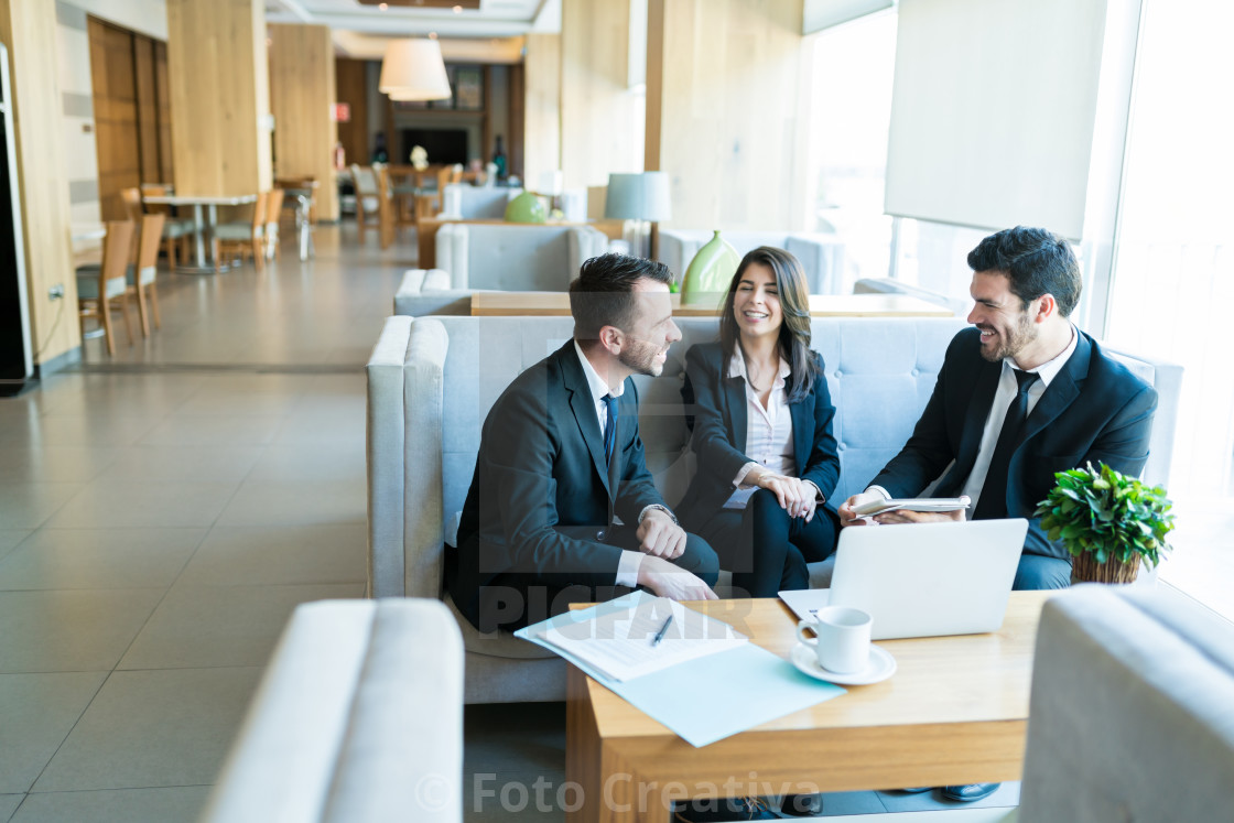 """Mid Adult Professionals Sharing A Light Moment In Lobby"" stock image"