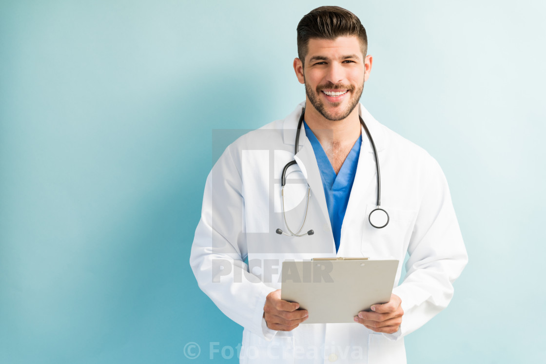 """Attractive Male Doctor Standing With Medical Record"" stock image"