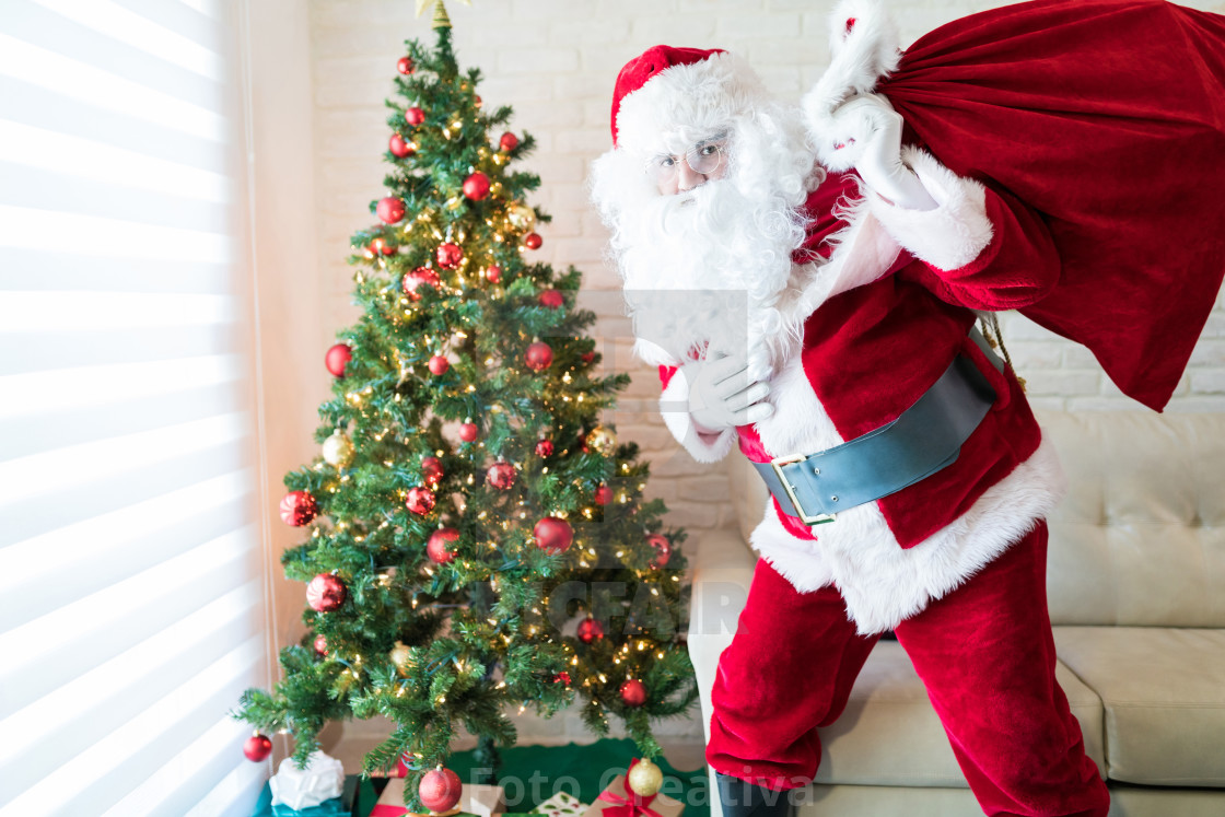 """Man in Santa costume by Christmas tree at home"" stock image"