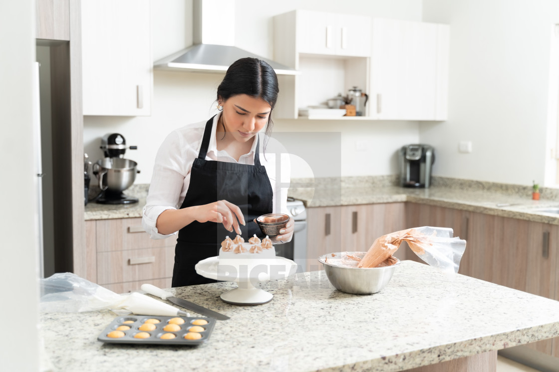 """Attractive Young Baker Giving Final Touch To Cake"" stock image"