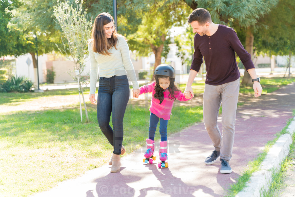 """Parents At Park Guiding Daughter To Skate"" stock image"