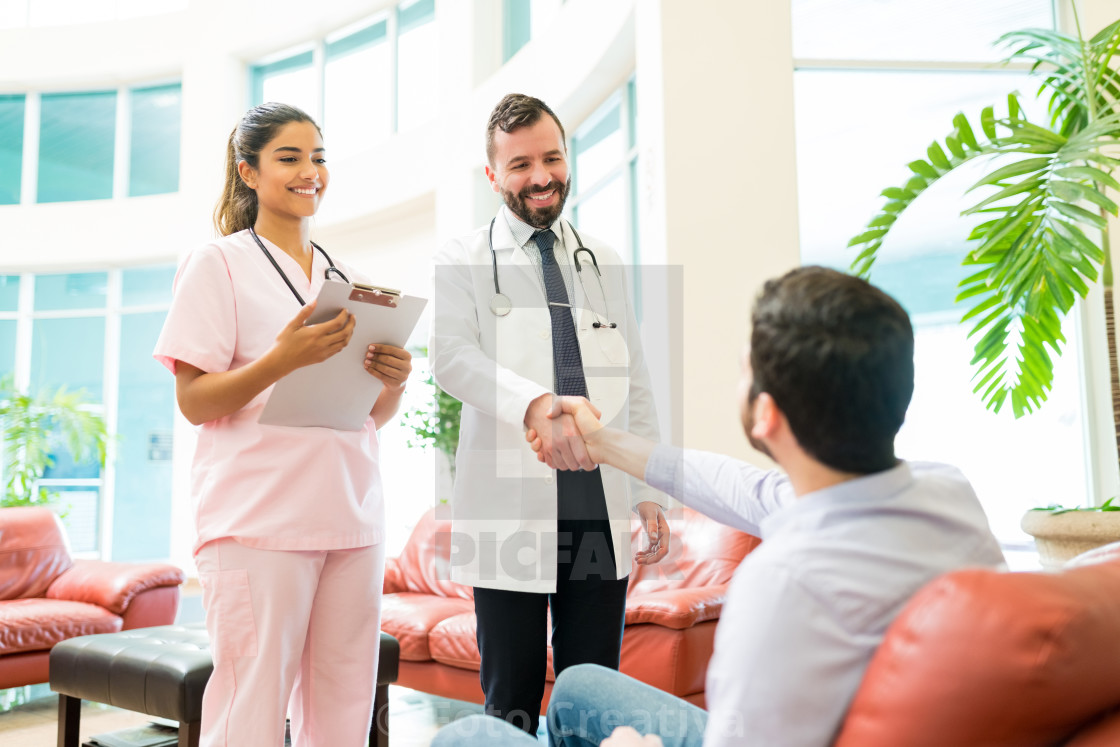 """Healthcare Workers Greeting Man Waiting At Hospital"" stock image"