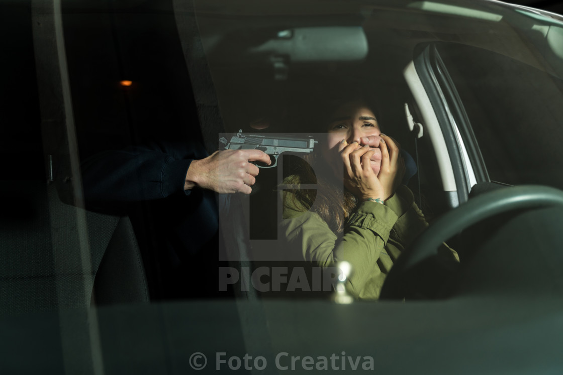 """Thief Covering Victim's Mouth While Scaring Her"" stock image"