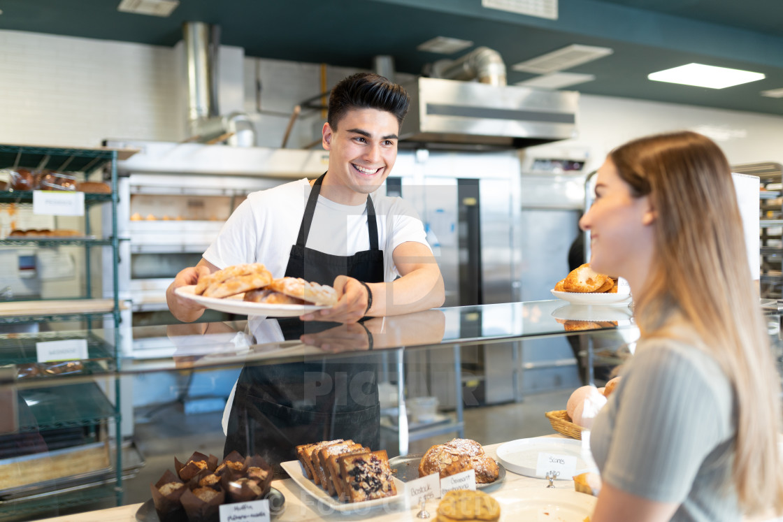 """Baker offering bread to customer"" stock image"