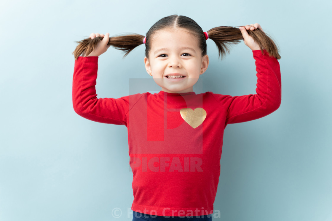 """Pretty girl showing off her ponytails"" stock image"