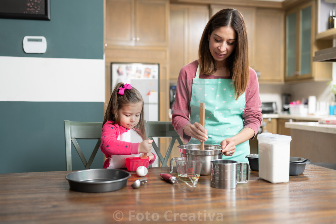 """Mom and daughter cooking together"" stock image"