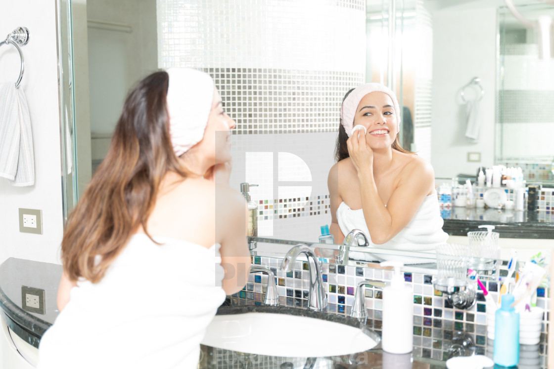 """Woman removing makeup in bathroom"" stock image"