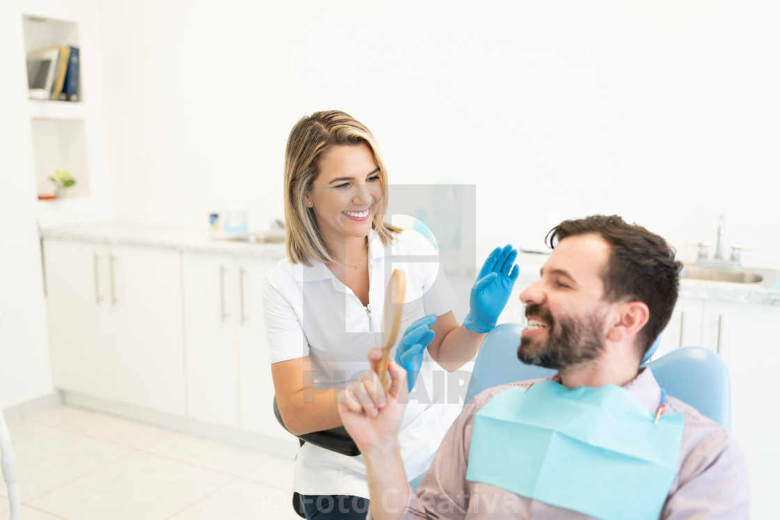 """Smiling Dentist With Patient At Clinic"" stock image"
