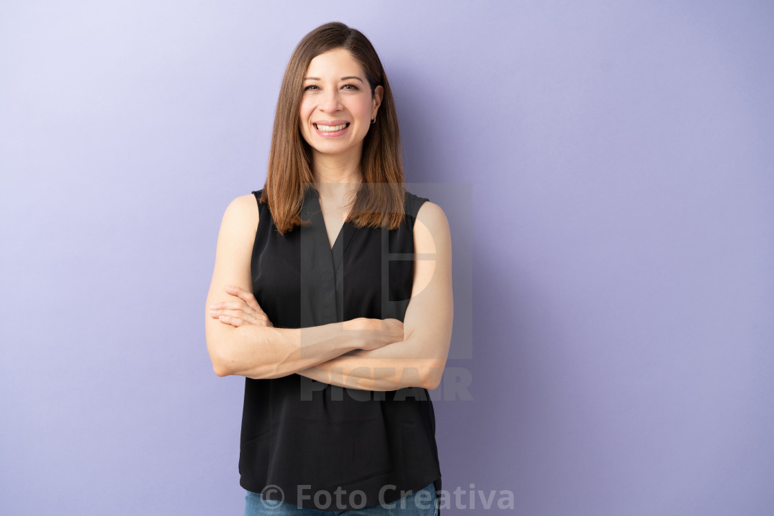 """Friendly woman standing with arms crossed"" stock image"