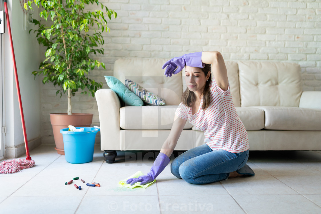 """Woman looking tired of cleaning her house"" stock image"