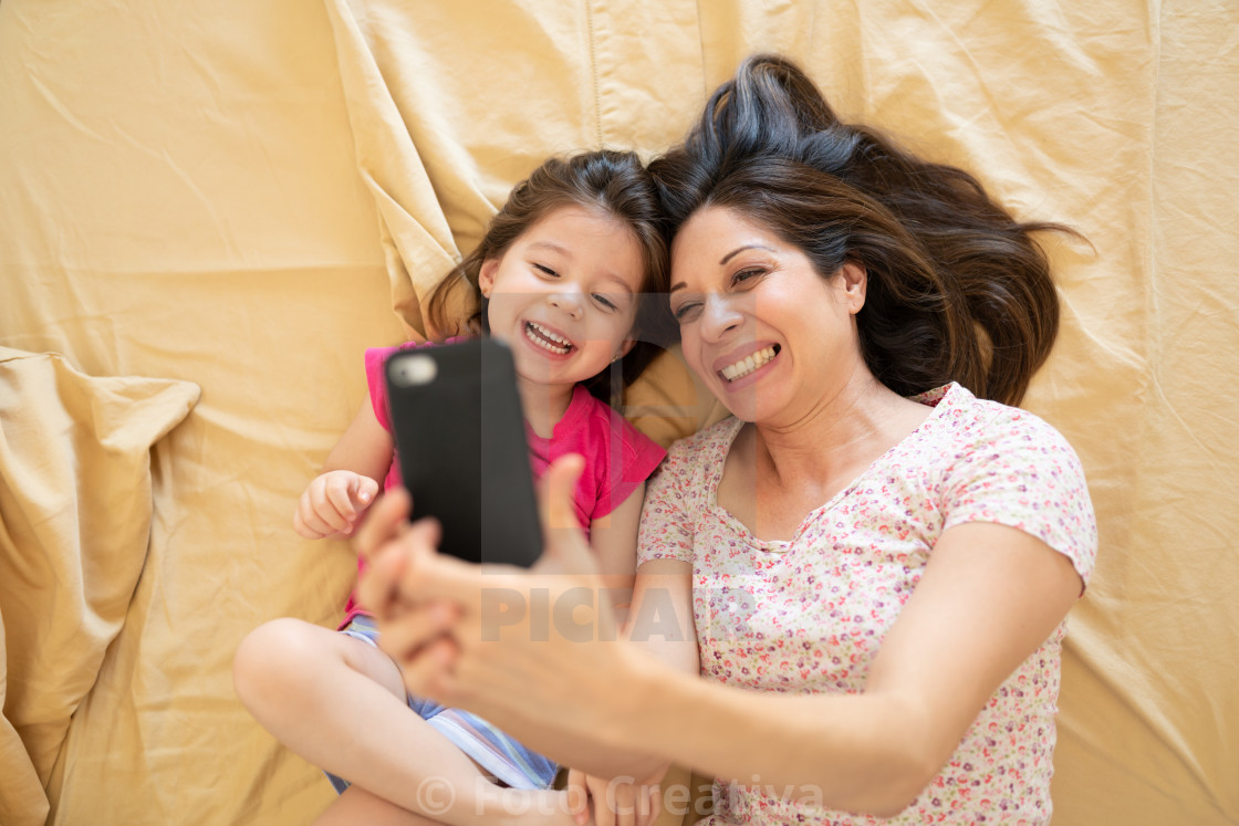 """Taking a selfie and wearing pajamas in bed"" stock image"