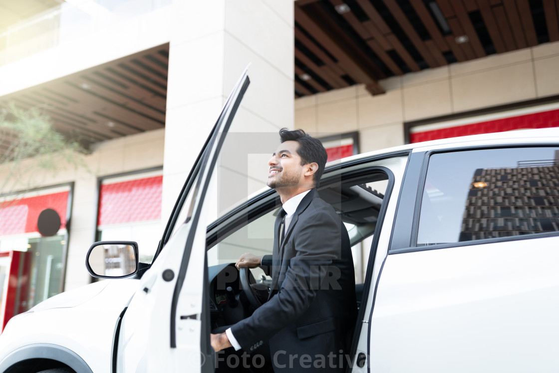 """Confident Businessman Getting Out From Car"" stock image"