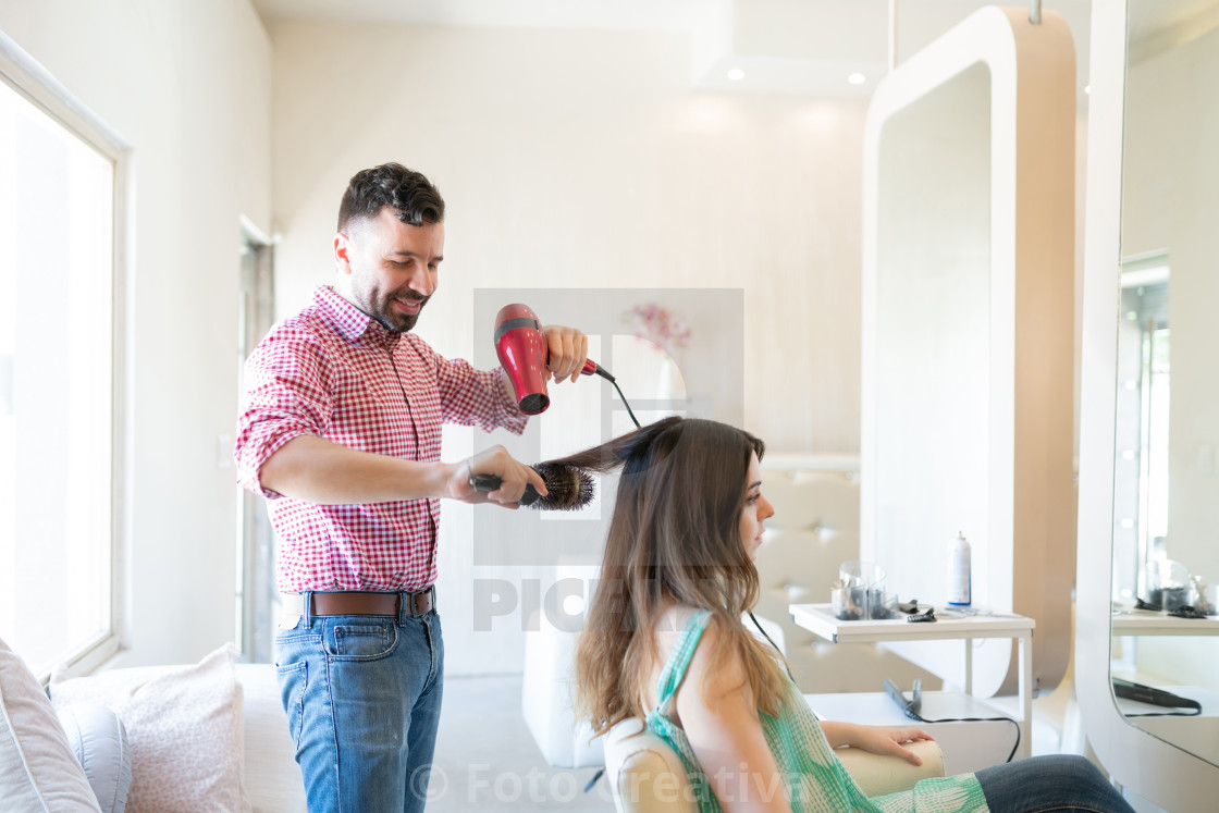 """Hispanic Male Hairstylist Styling Hair Of Client"" stock image"