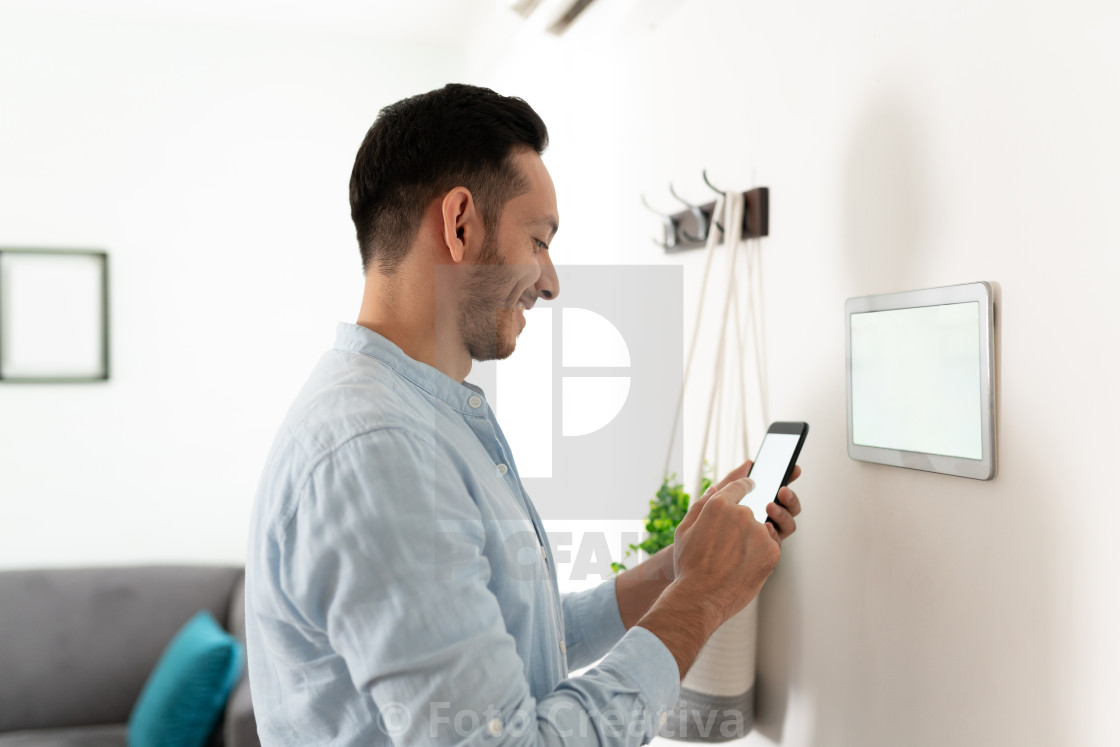 """Setting up his smart home devices"" stock image"