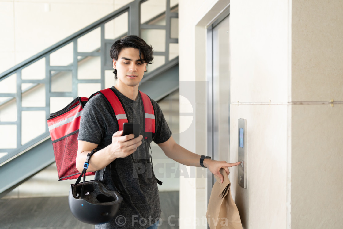 """Delivery Man With Parcel Waiting For Elevator In Apartment"" stock image"