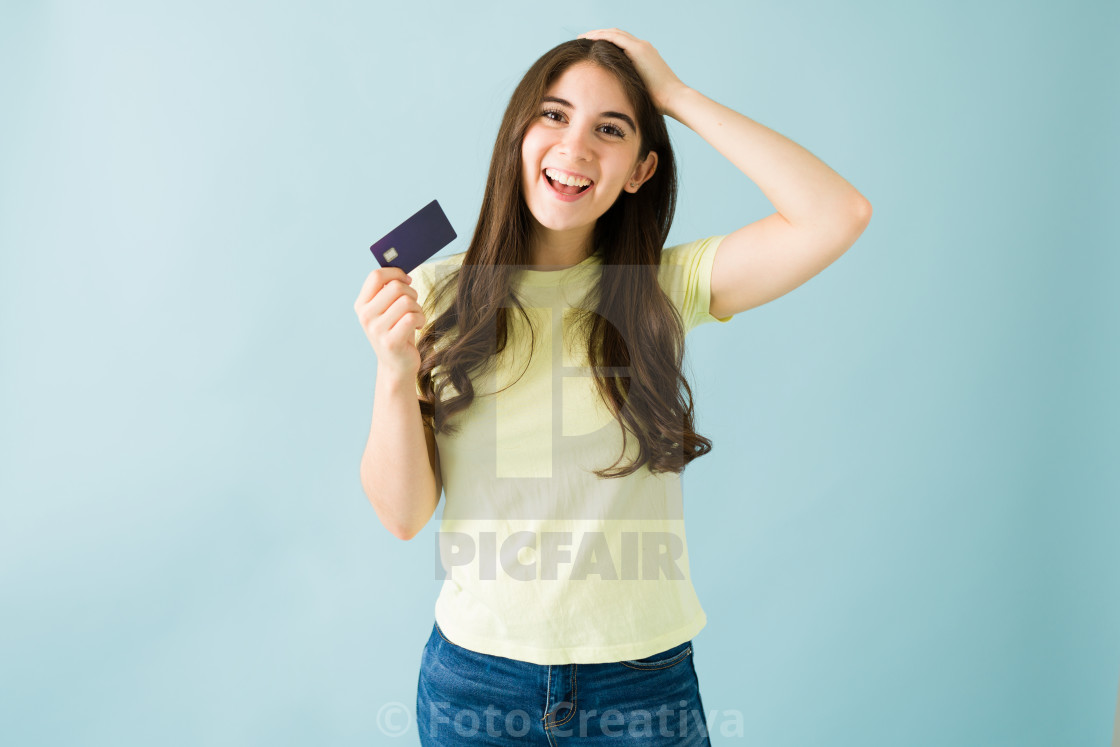 """Portrait of an excited young woman holding up her credit card"" stock image"