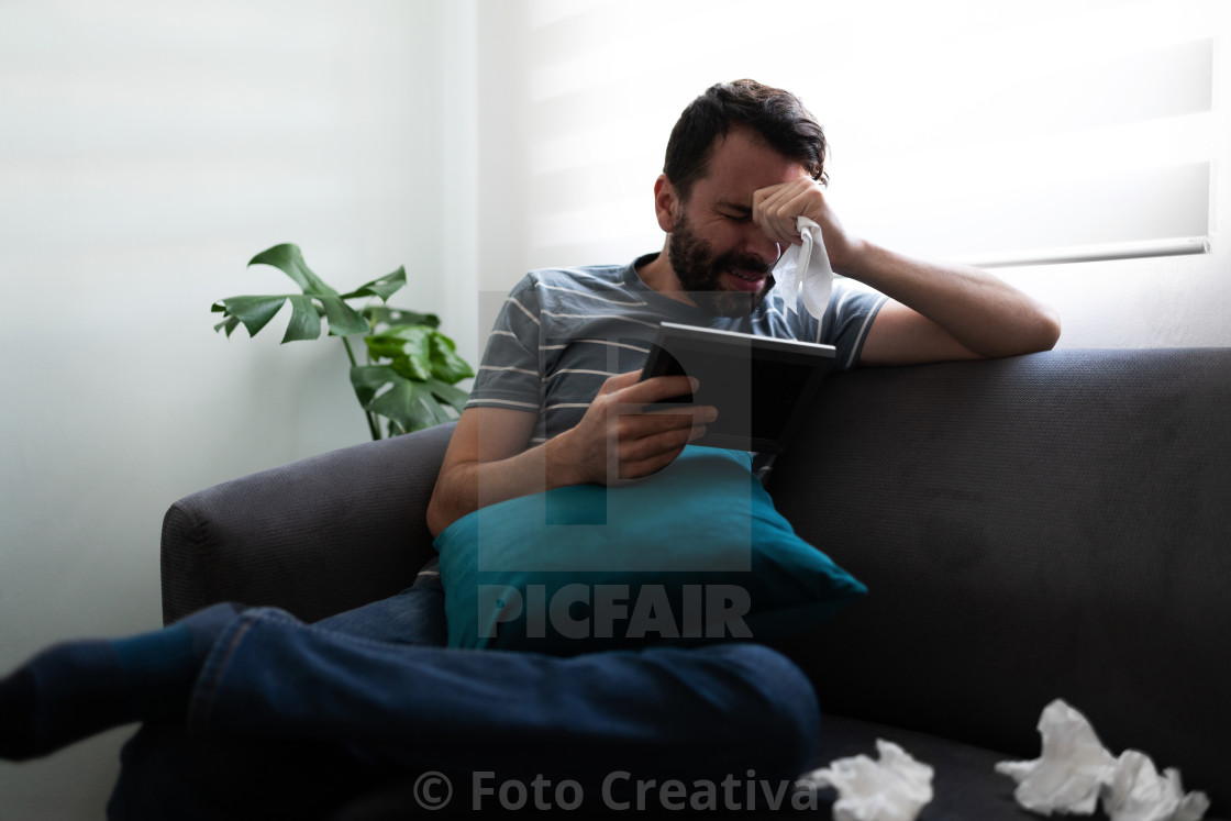 """Adult man holding a photograph and sobbing"" stock image"
