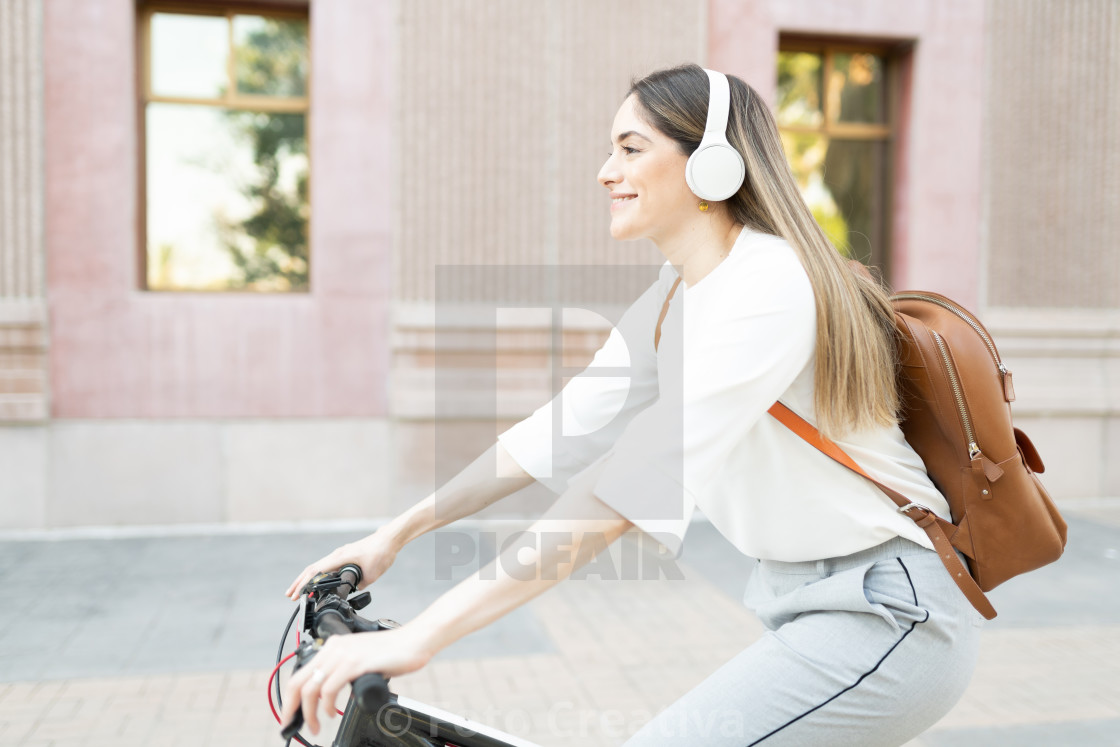 """Profile of a smiling woman with a business outfit on her bike commute to work"" stock image"