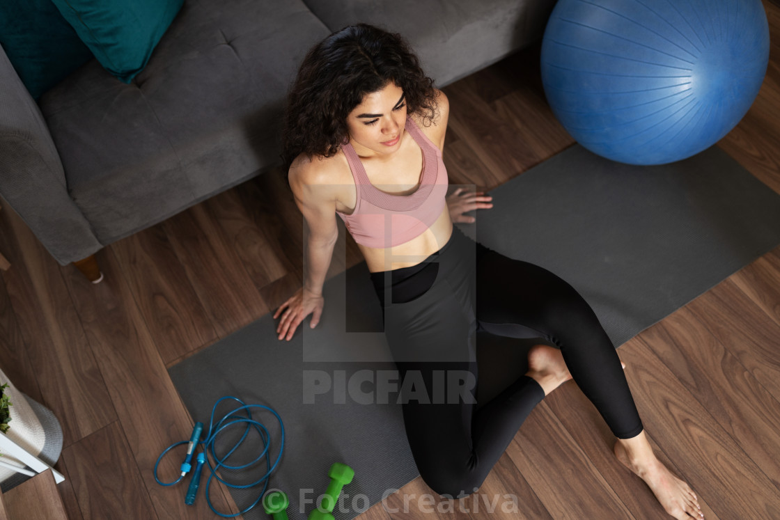"""Woman with a fitness lifestyle resting after a home workout"" stock image"