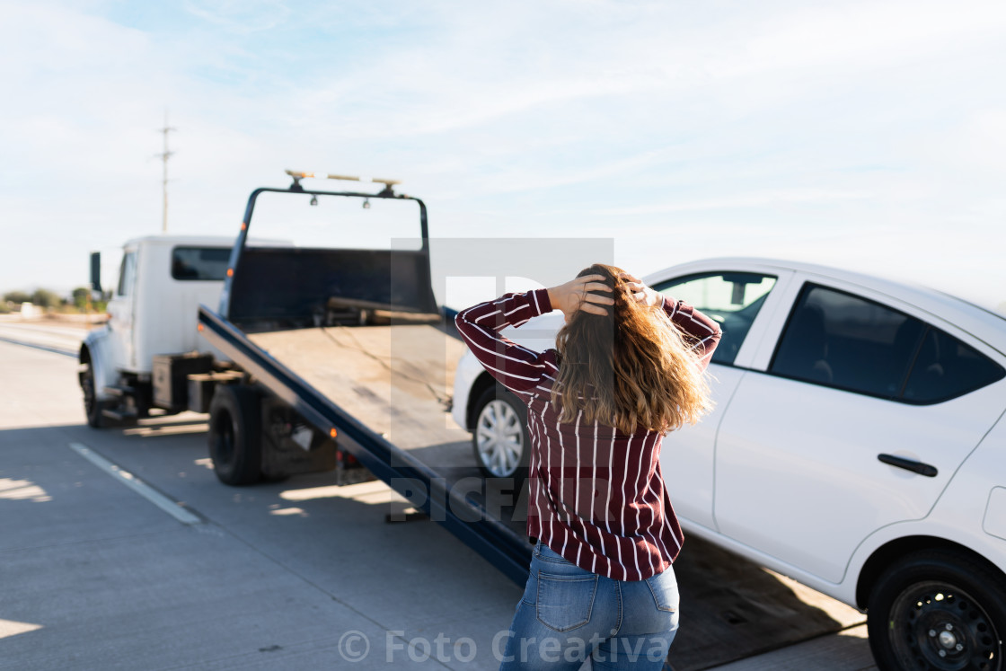 """Angry woman seen from behind and watching her car on a tow truck"" stock image"