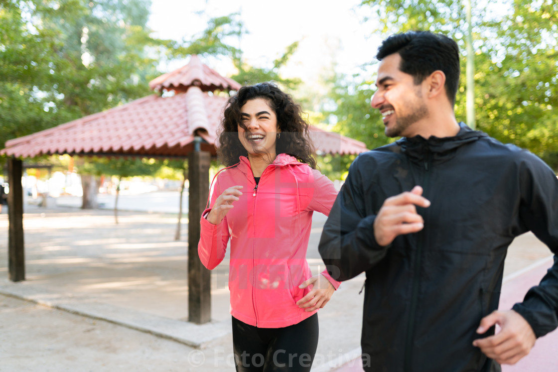 """Happy couple laughing and running in the park"" stock image"