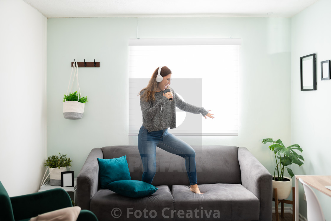 """Caucasian woman with a cheerful expression dancing on her couch"" stock image"