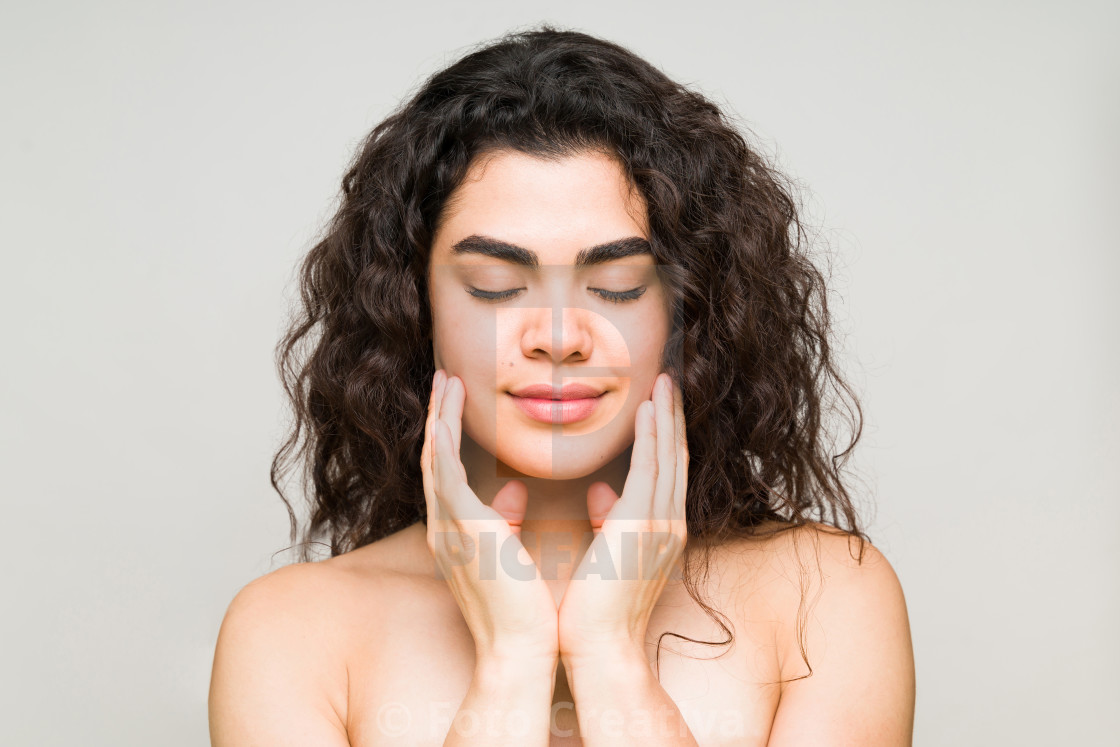 """Latin woman with her eyes closed and touching her healthy skin"" stock image"
