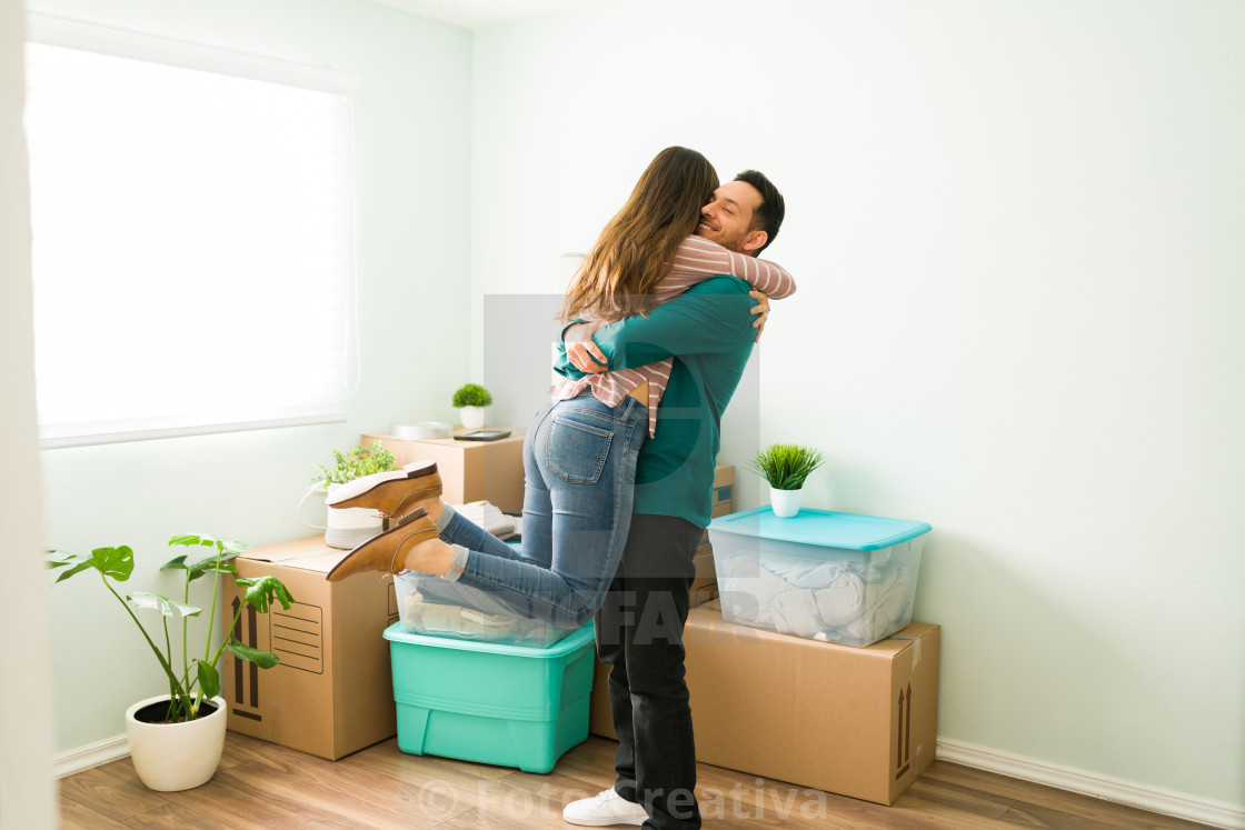 """Married couple celebrating after moving into a new apartment"" stock image"
