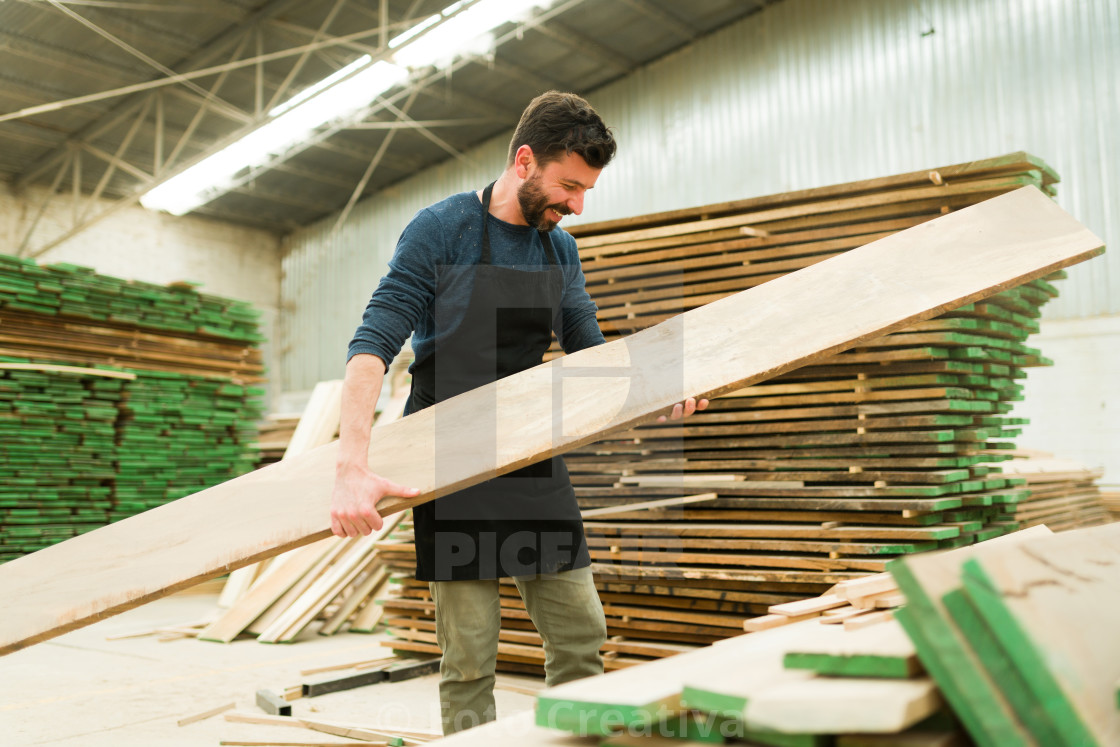 """Smiling man picking up a wood board in a workshop"" stock image"