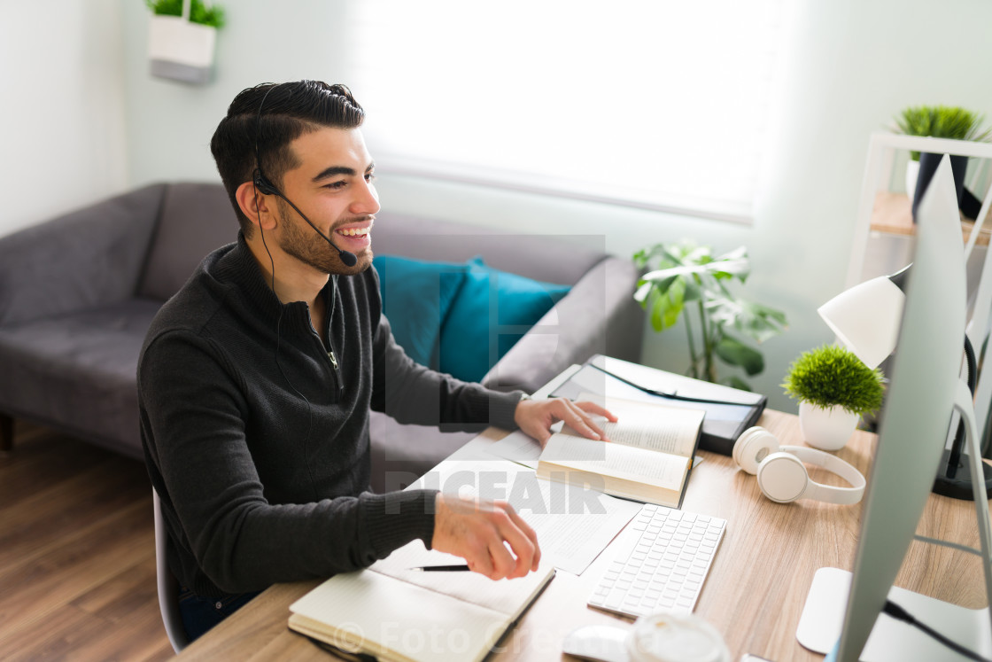 """Young guy is very happy to be working remotely as a translator"" stock image"